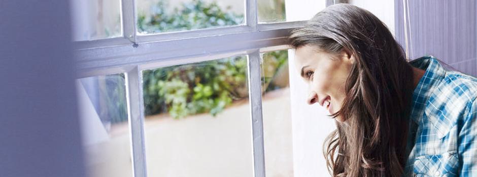 Femme à la fenêtre qui attend son colis.